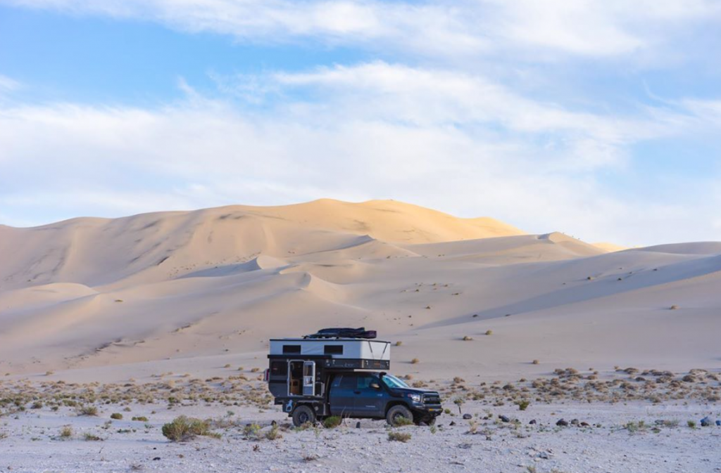 Toyota Tundra Camper in the middle of a sandy desert with cloudy blue skies above.