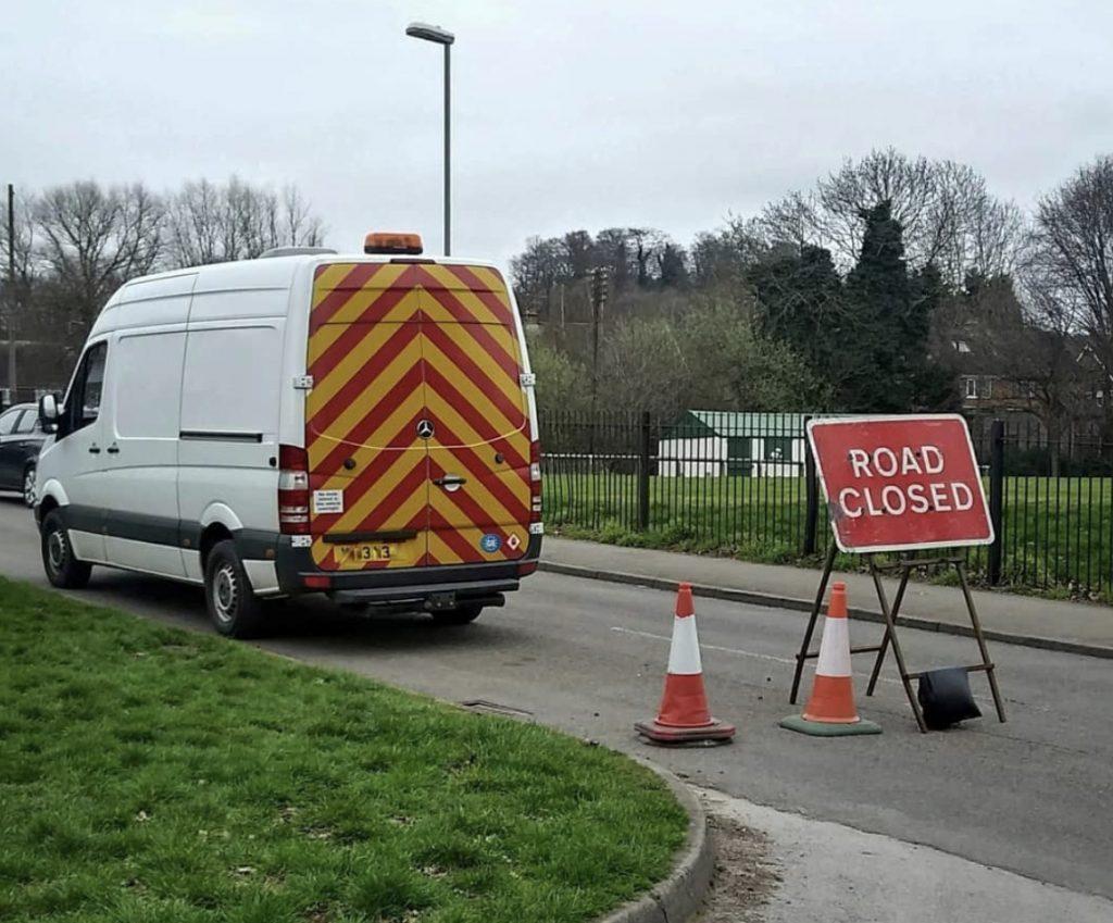 Stealth campers - van blending in, parked behind a road closed sign.