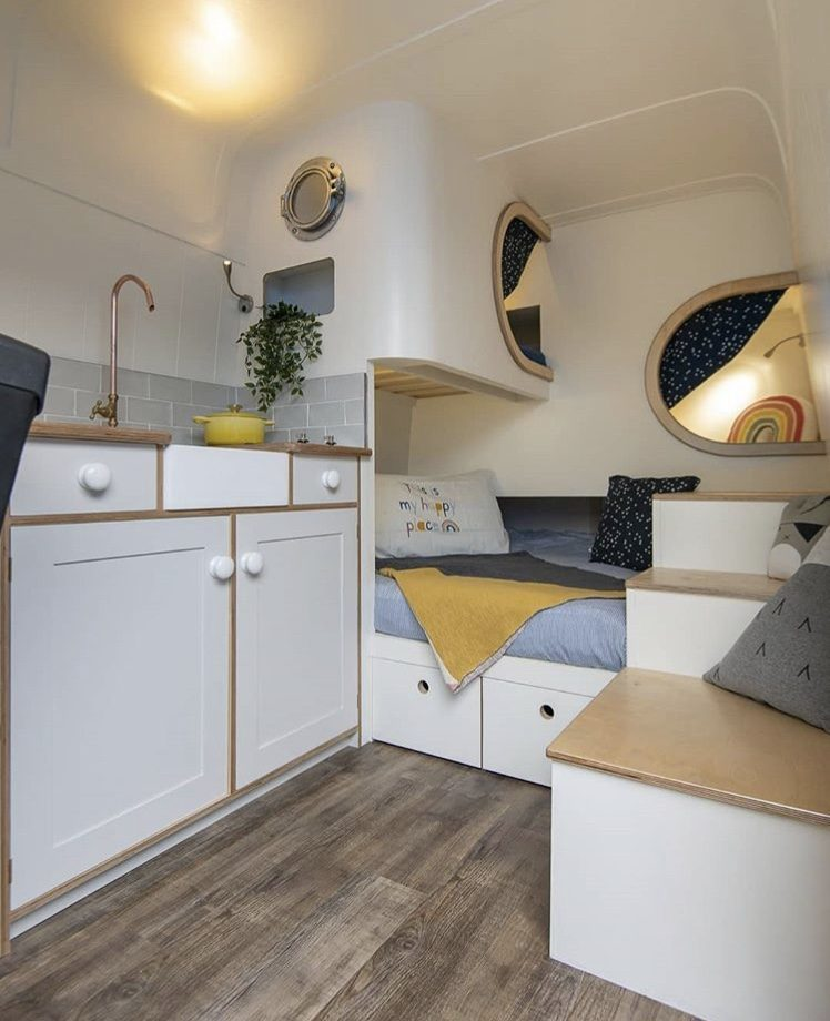 White van interior with sleeping pods at back.