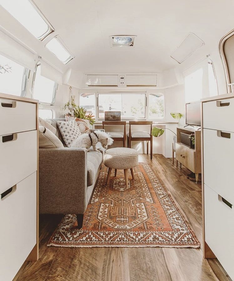 White airstream with red patterened rug.