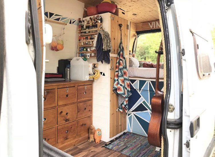 Wooden van interior with blue patterened drawers.
