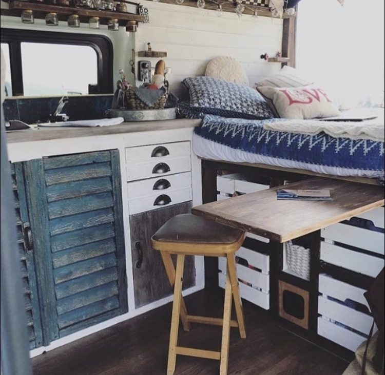 Blue and white van interior with fixed double bed at back.