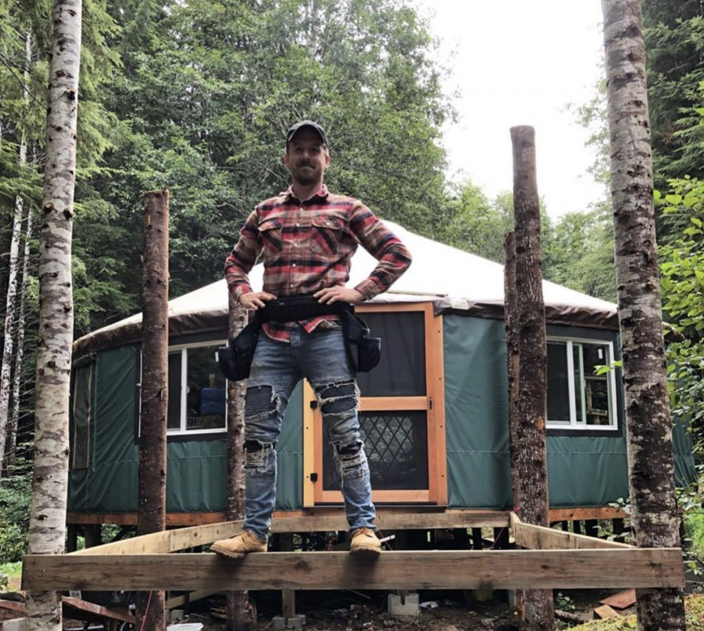 Jake standing in front of his yurt house. Tiny House YouTube.
