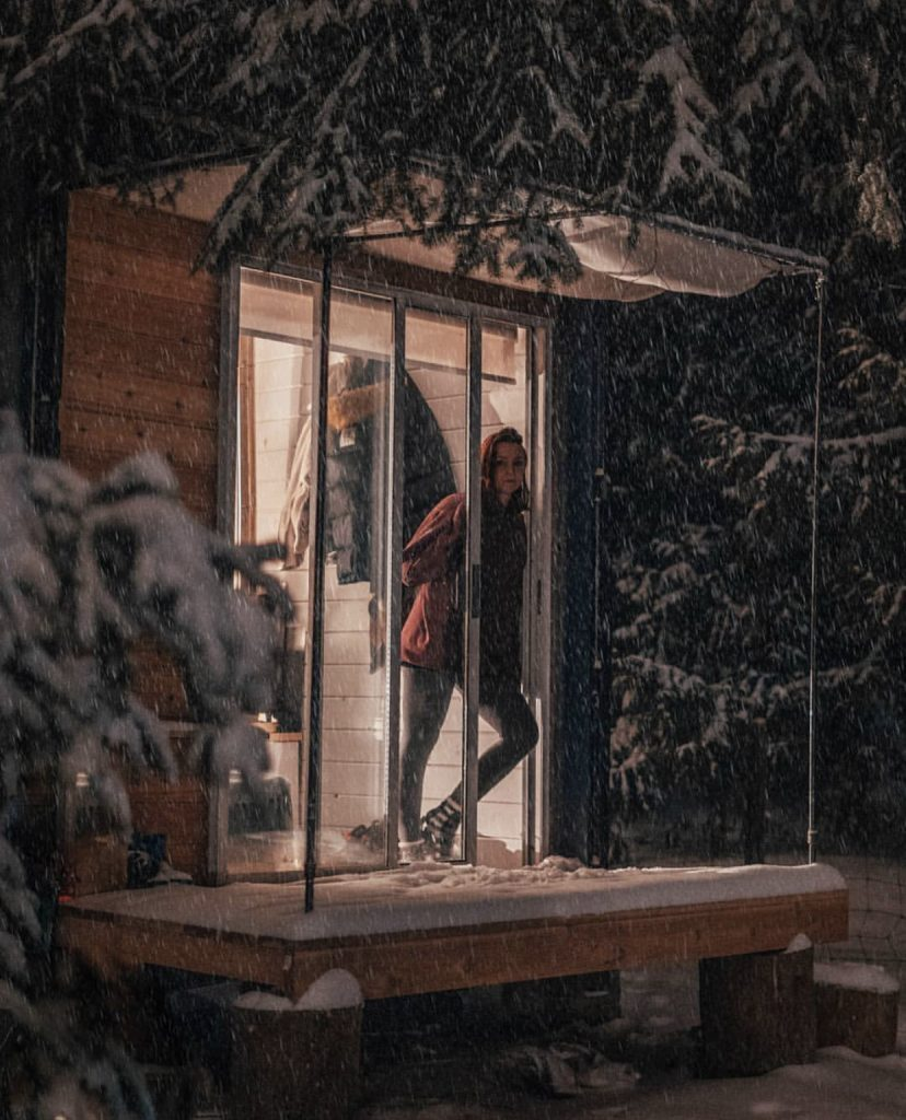 Shipping container home lit up in snow at night.