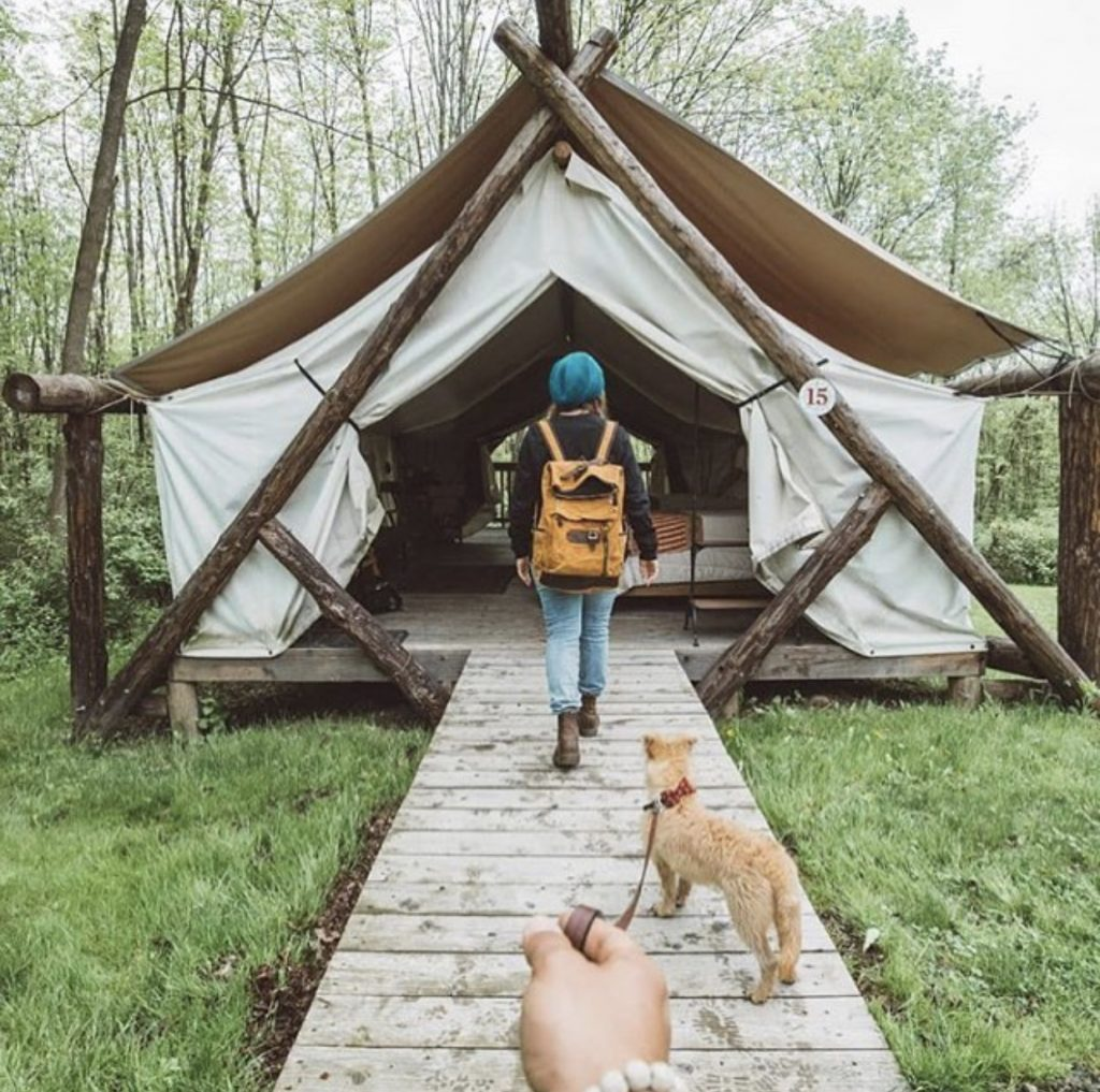 Woman and dog walking into tewnt home. Tiny house youtube.