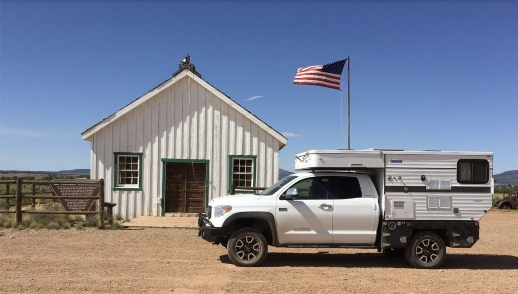 Four wheel camper outside barn with American flag