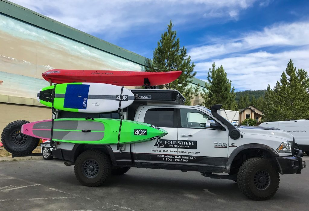 The new camper kitted out with a surfboard, paddle board and a kayak on the roof. Affordable campers