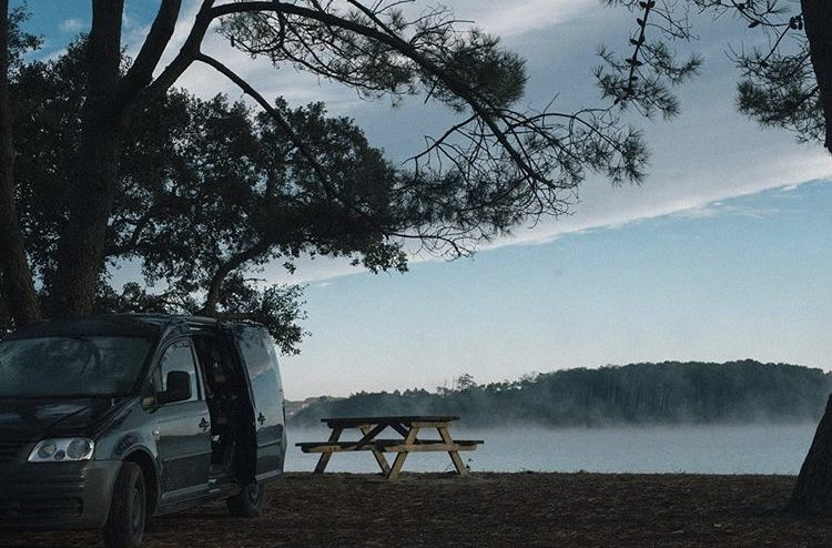 VW Caddy Camper infront of lake next to picnic table.
