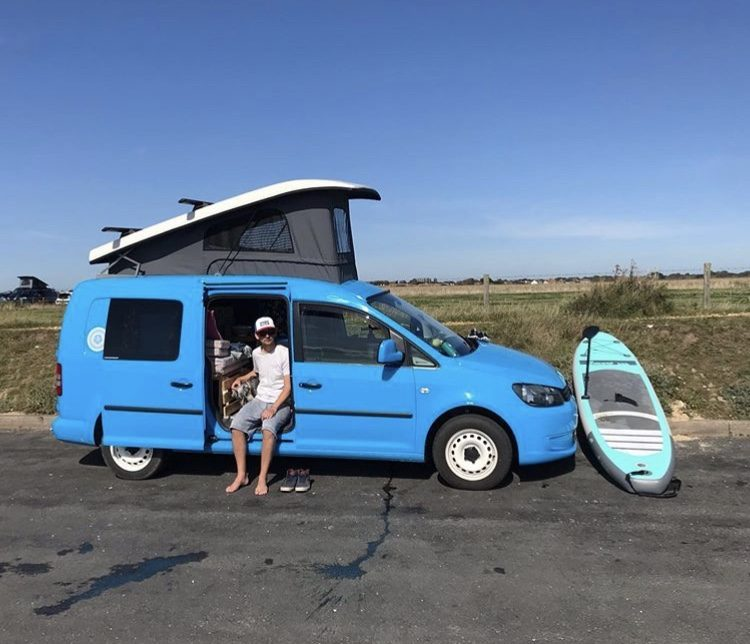 Camper with a pop top, paddleboard next to it.