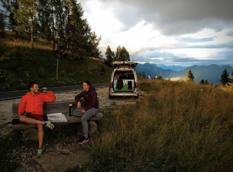 People eating pizza on bench in front of camper in mountains.