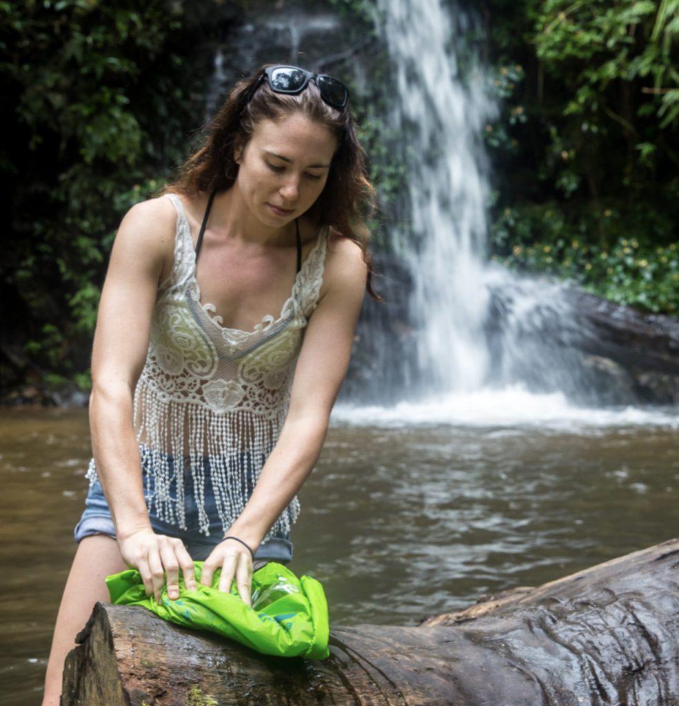 Woman using RV washing machine Scrubba Wash Bag at a waterfall