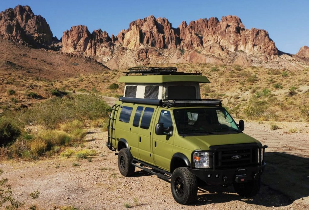 Best Small RV - Green Sportsmobile classic 4x4 with pop top in front of Rocky Mountains