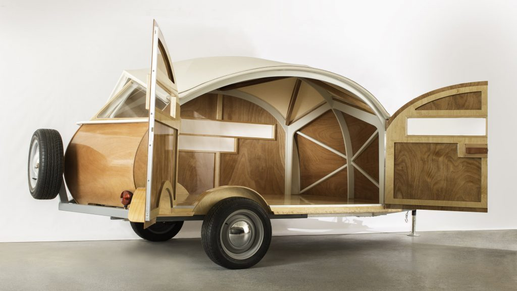 Best teardrop campers - the all wooden Hütte Hut with its doors wide open, showing a rich wooden interior with interesting cross beams.