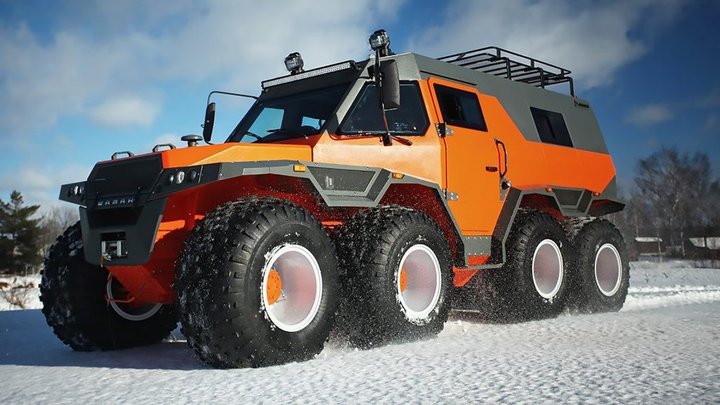 Avtoros Shaman on the snow. A bright orange monster camper with eight ginormous wheels!