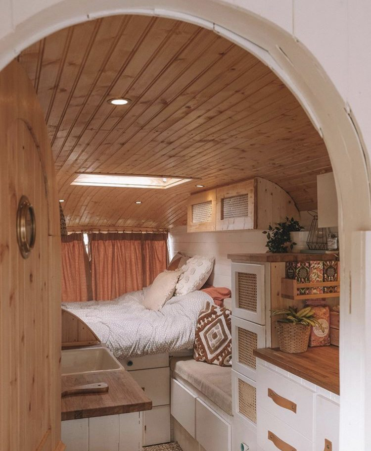 Custom van ideas- wooden van interior with bed, shot through arched doorway.
