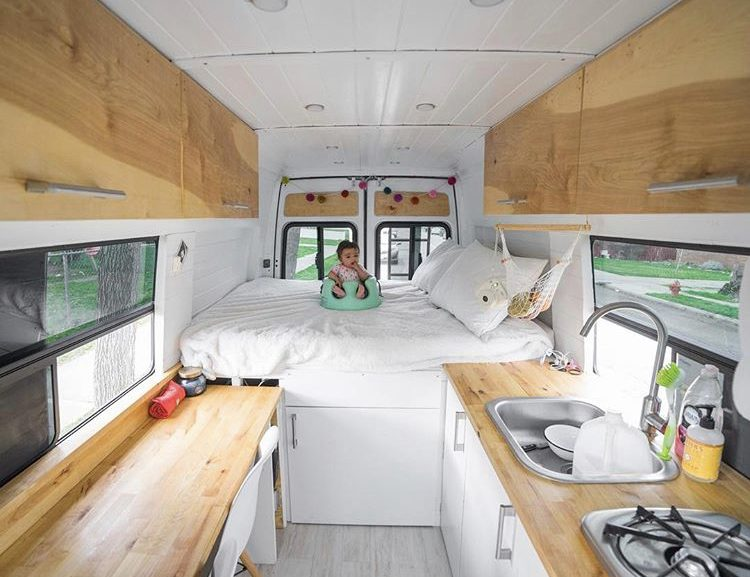 Custom van ideas - white interior of van with bed at back and wooden work top and table on either side.