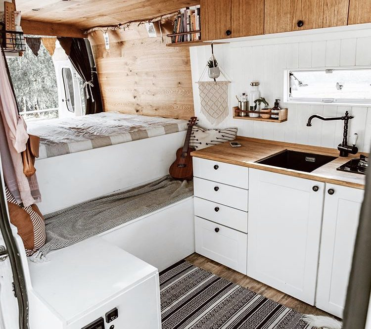 Custom van ideas - white interior with double bed at back with bench infront and kitchen to the side.