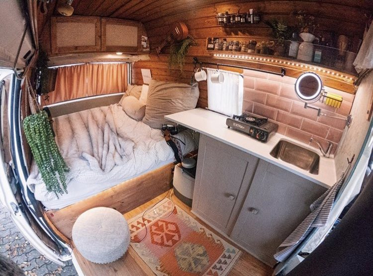Interior of van with pink tiling, rug and large cosy double bed at back.