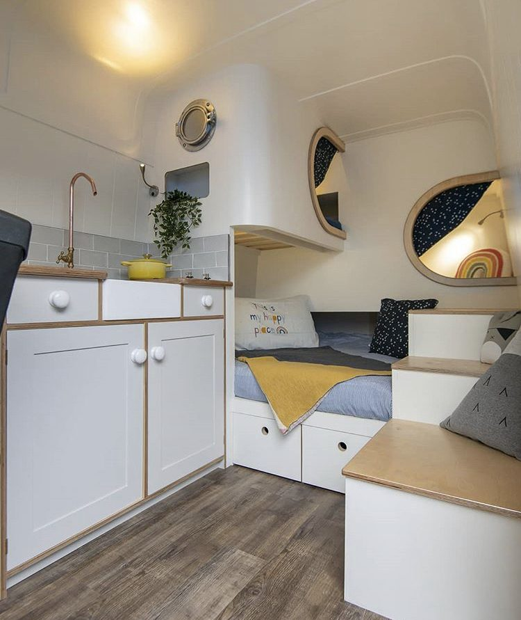 White van interior with kitchen, double bed and kids bed pods.