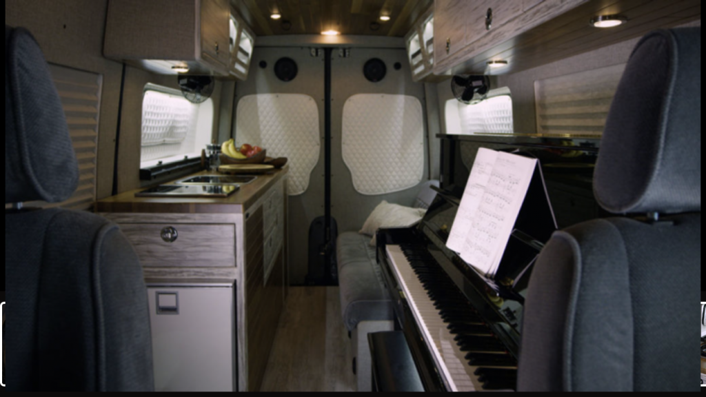 Camper van conversion with piano opposite the kitchen.