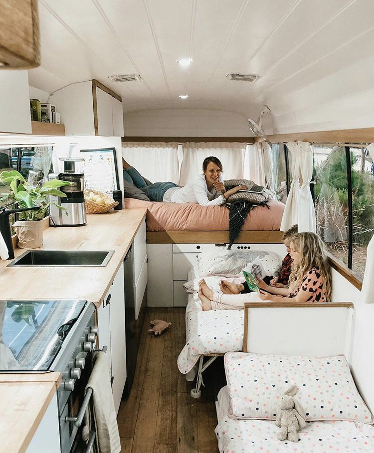 Custom van ideas- woman lying on bed with two kids reading books on their single beds opposite kitchen.