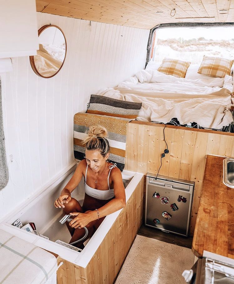 Woman sat in bathtub inside her van at the foot of static double bed.