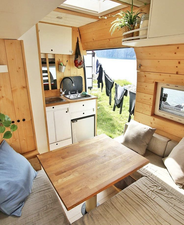 Wooden interior of van with U-shaped sofa and bulkhead kitchen