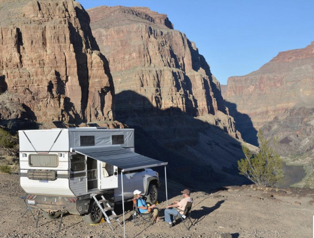Hawk Truck camper exterior with roof popped and awning open infront of Rocky Mountains.