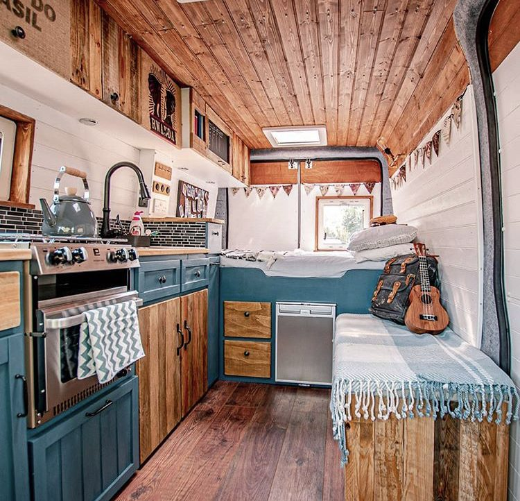 Custom van ideas - van with static bed at back, wooden ceiling, blue kitchen on one side and bench seat on the other.