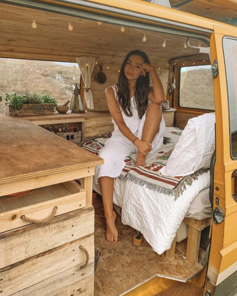 woman sat on bed in wooden campervan interior