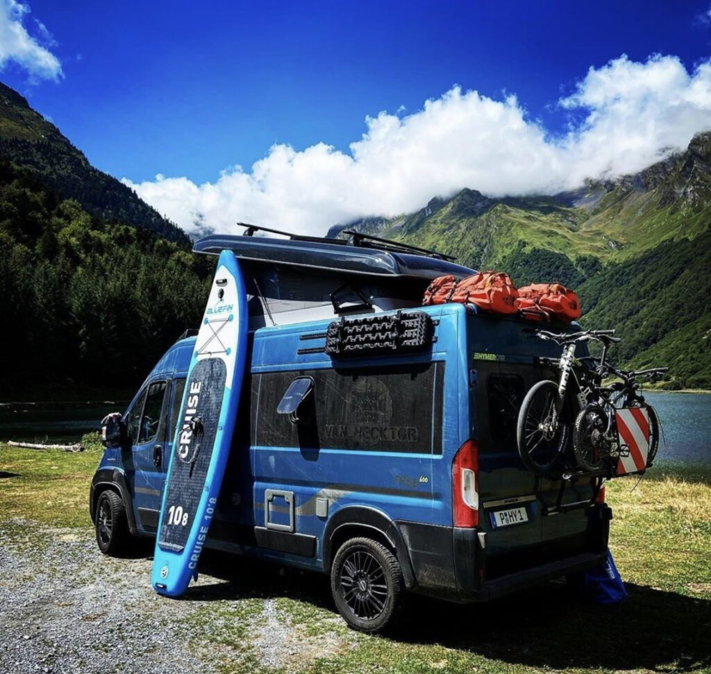 Outside of camper with bikes, paddleboard and gear on roof