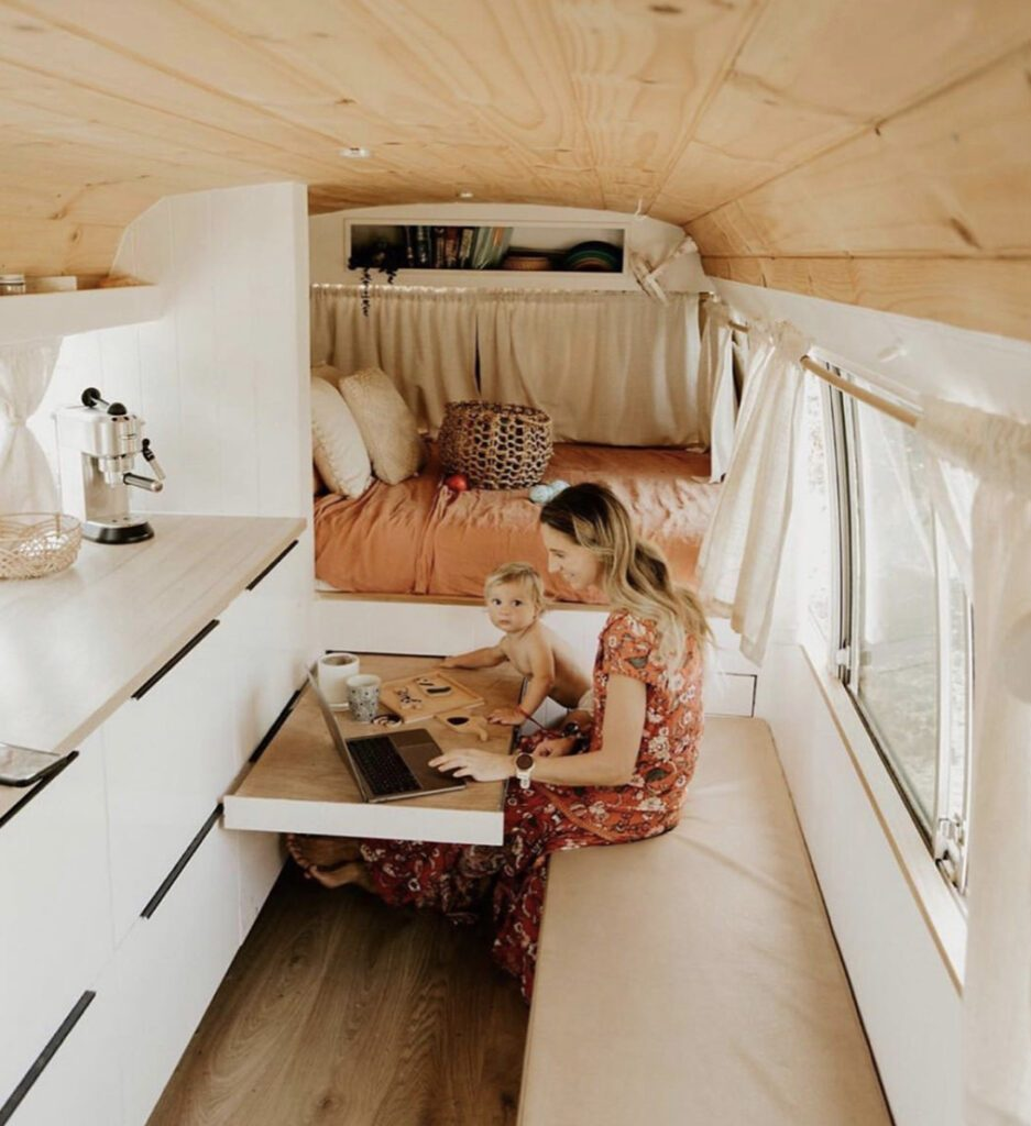 Small RV - woman and baby sat at pull out table