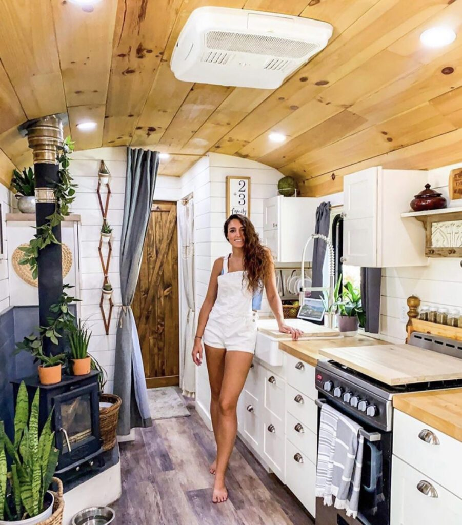 Woman stood in her camper's kitchen with frames on the wall and a fireplace