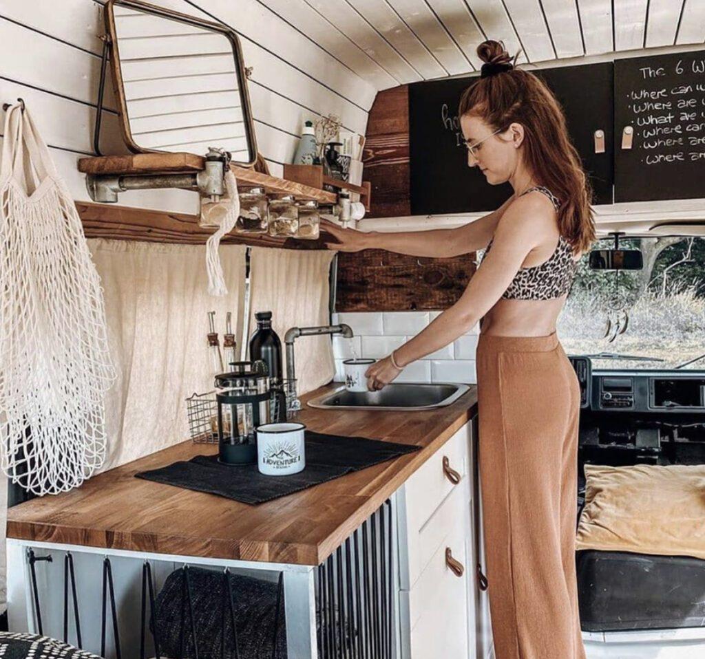 Small RV - woman using tap inside camper