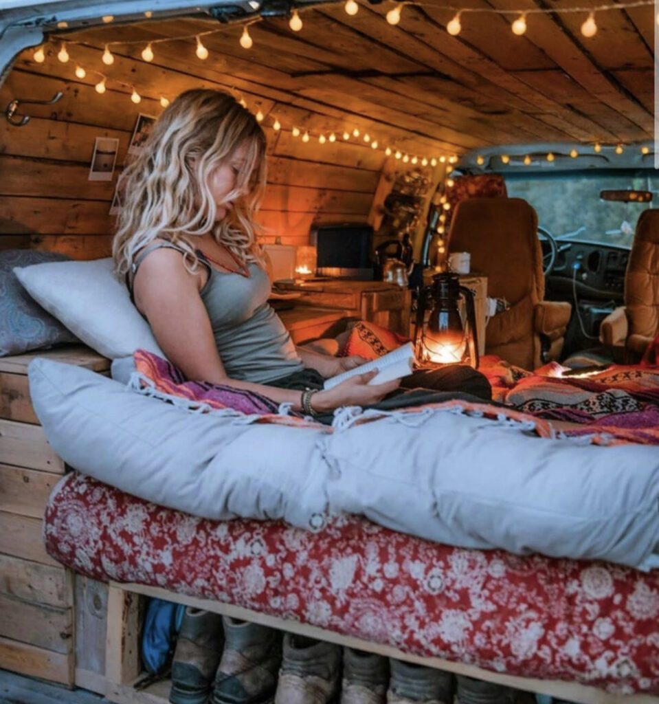 Woman sat reading in her van home on the bed with fairy lights on