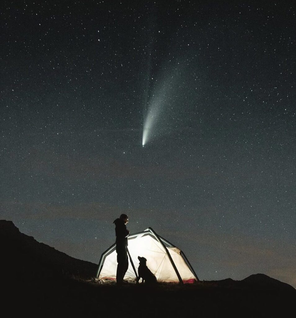 Sillouette of man and dog against lit up tent under the stars