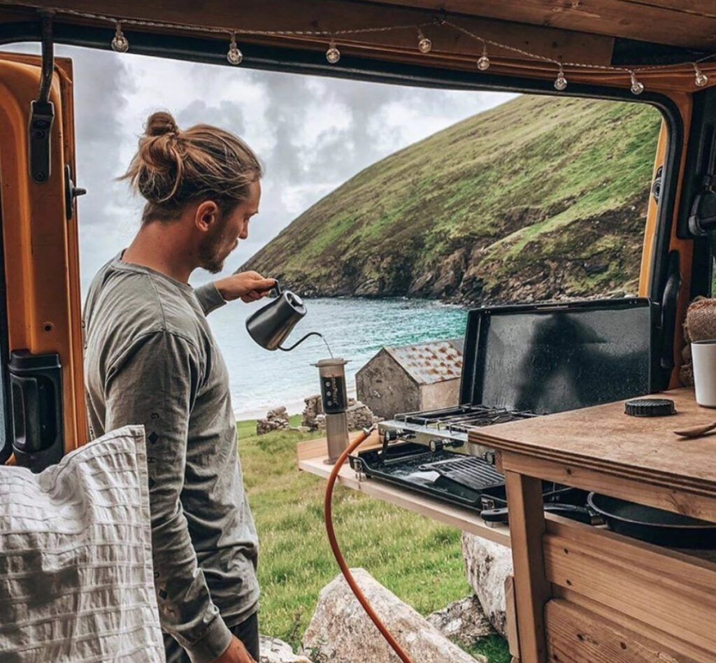 Man making coffee outside van with view of lake