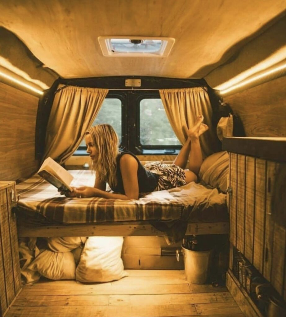 Van Home - woman laid on her be in her camper reading a book