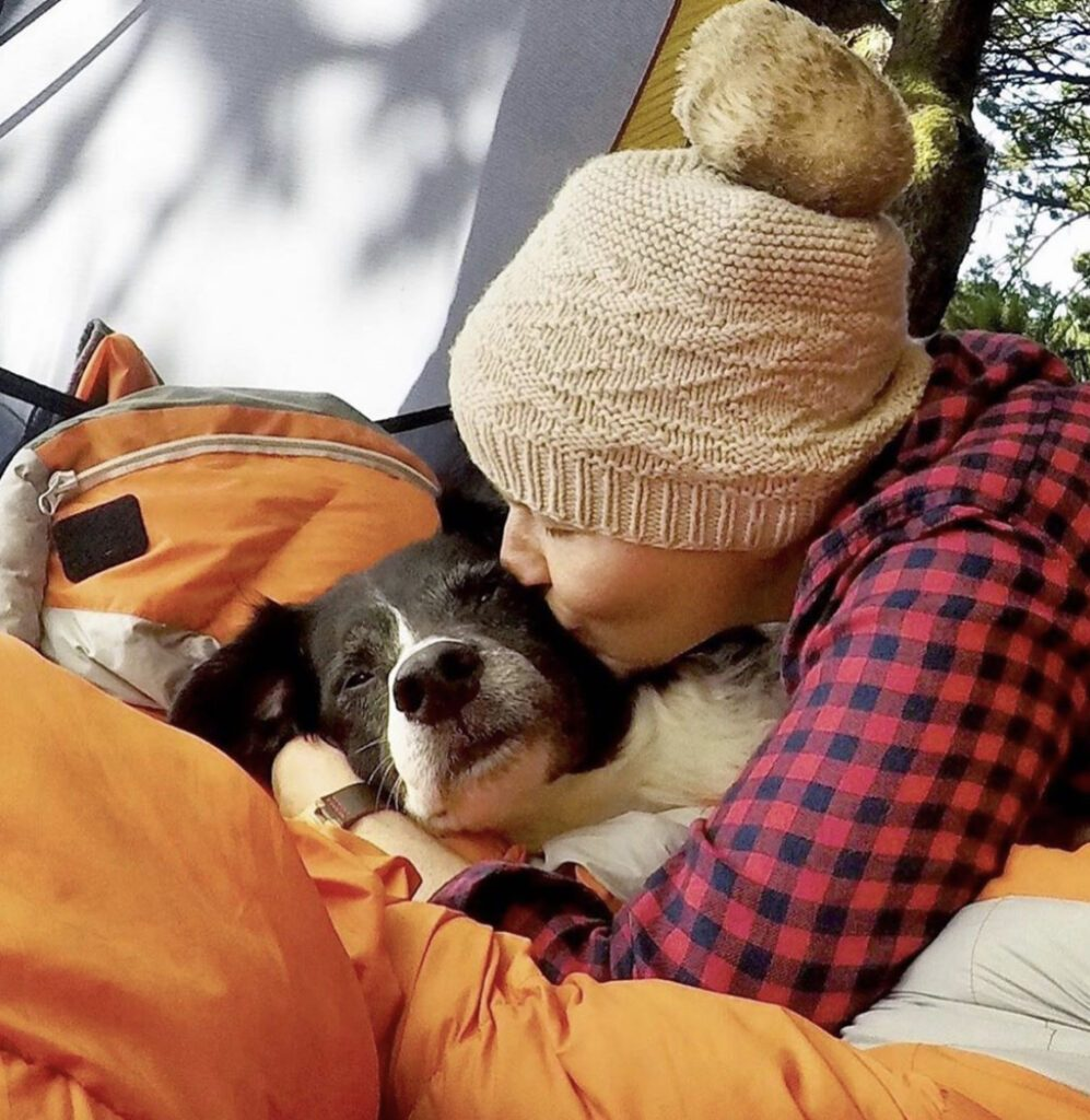 Person snuggling their dog in a tent
