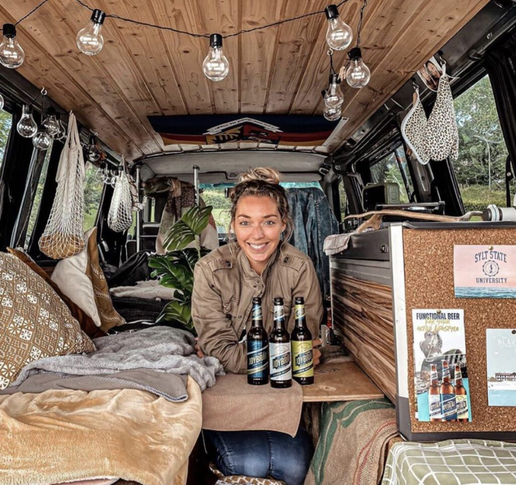 Small RV - woman sat at multi-functional bed/seat/table inside van