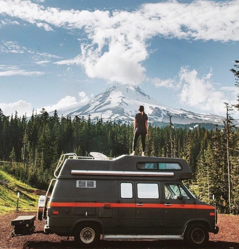 Woman stood ontop of her camper infront of a forest and mountains