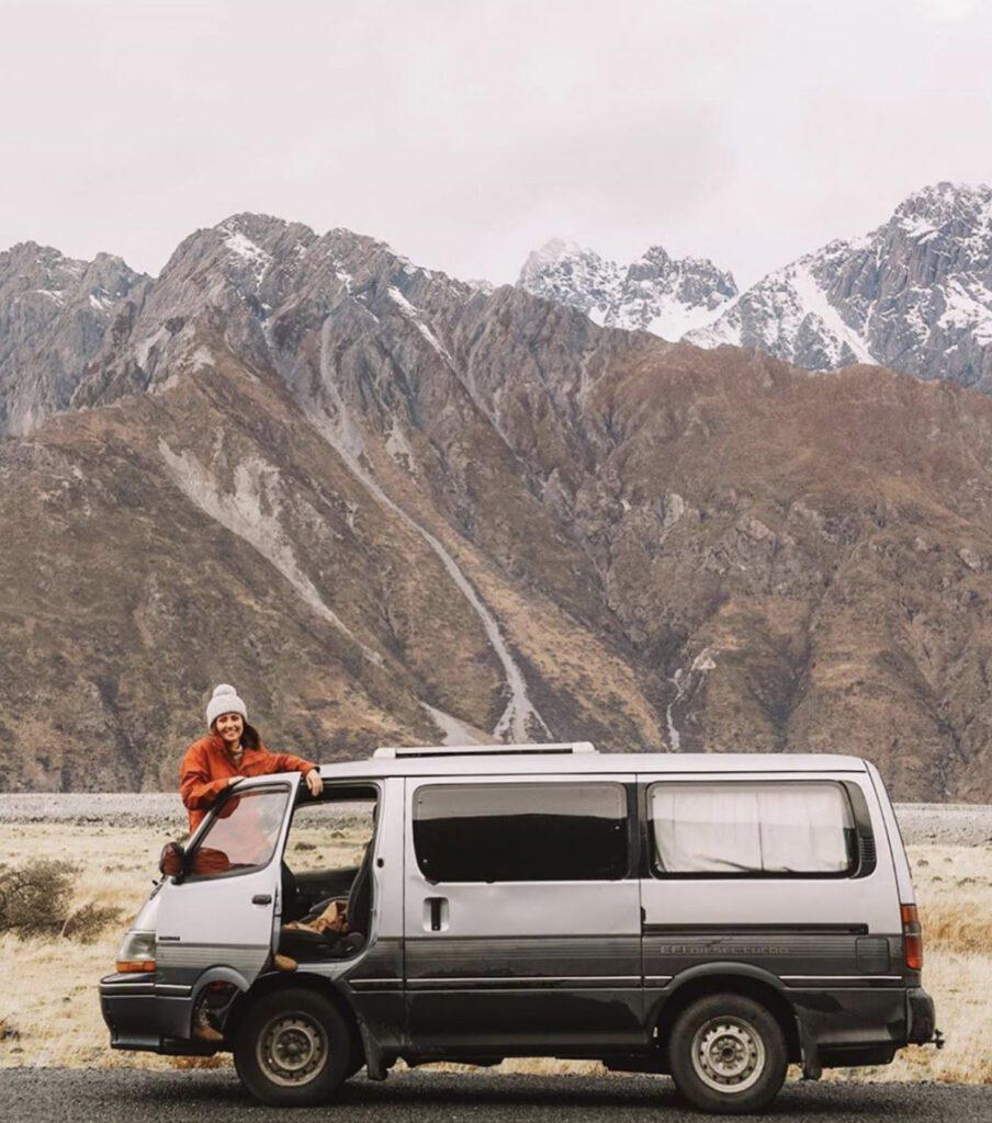 Van camping - woman standing out of front door of van infront of mounatains