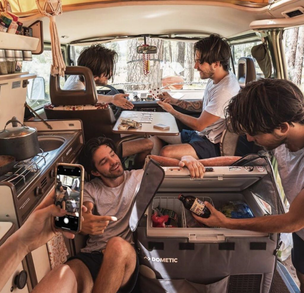 Man inside camper five times by photoshop, using phone, fridge and playing cards