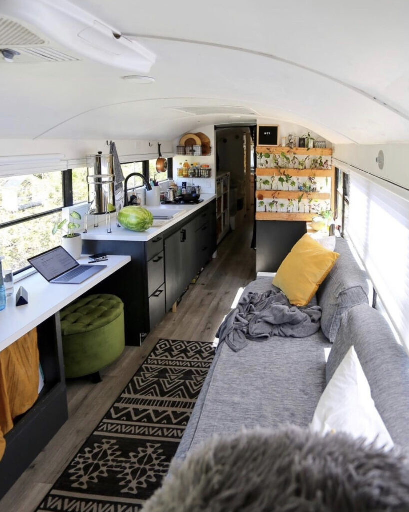 Skoolie conversion - white bus with black kitchen cabinets, grey sofa and plant wall