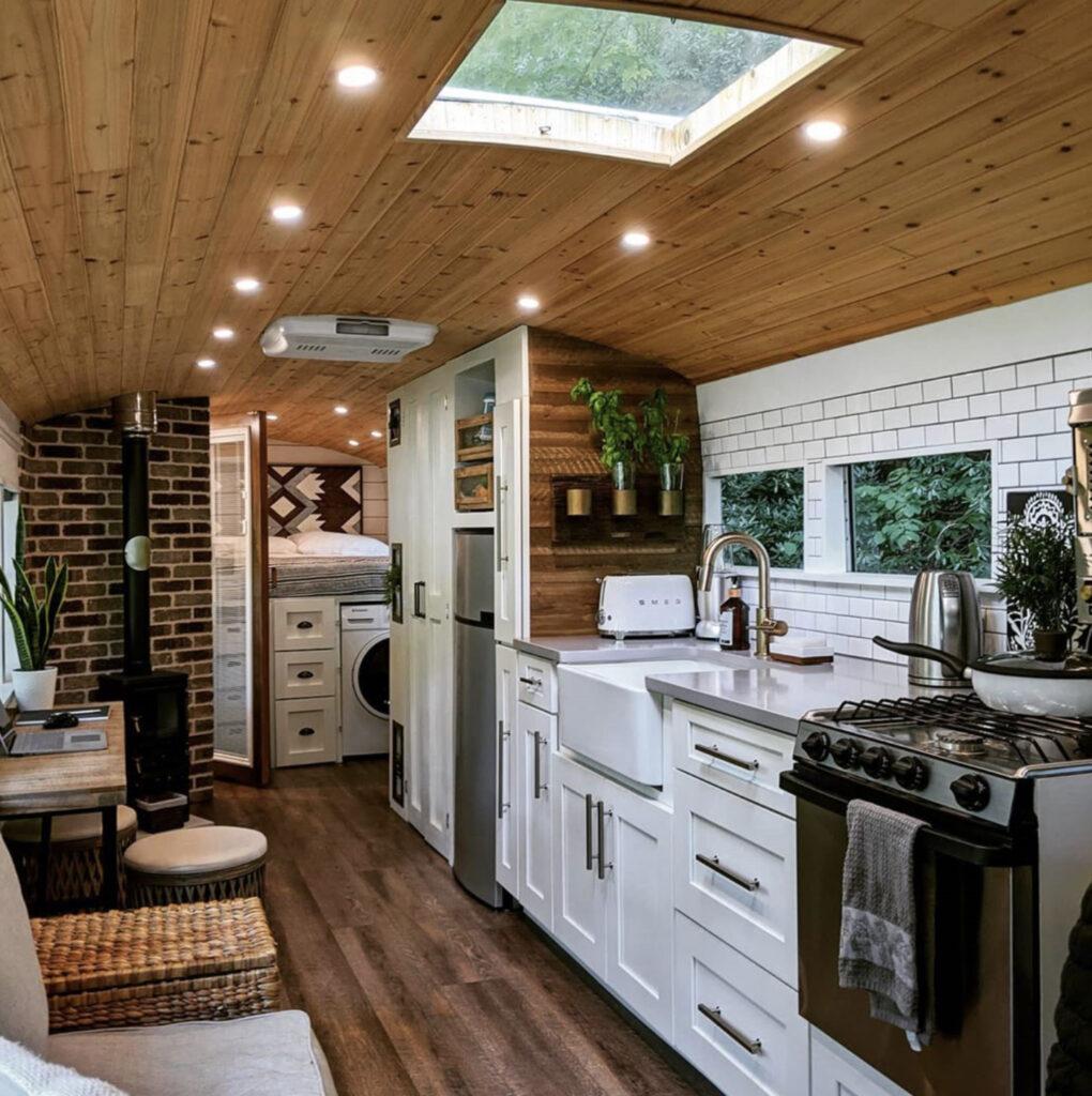 Large white kitchen in skoolie conversion
