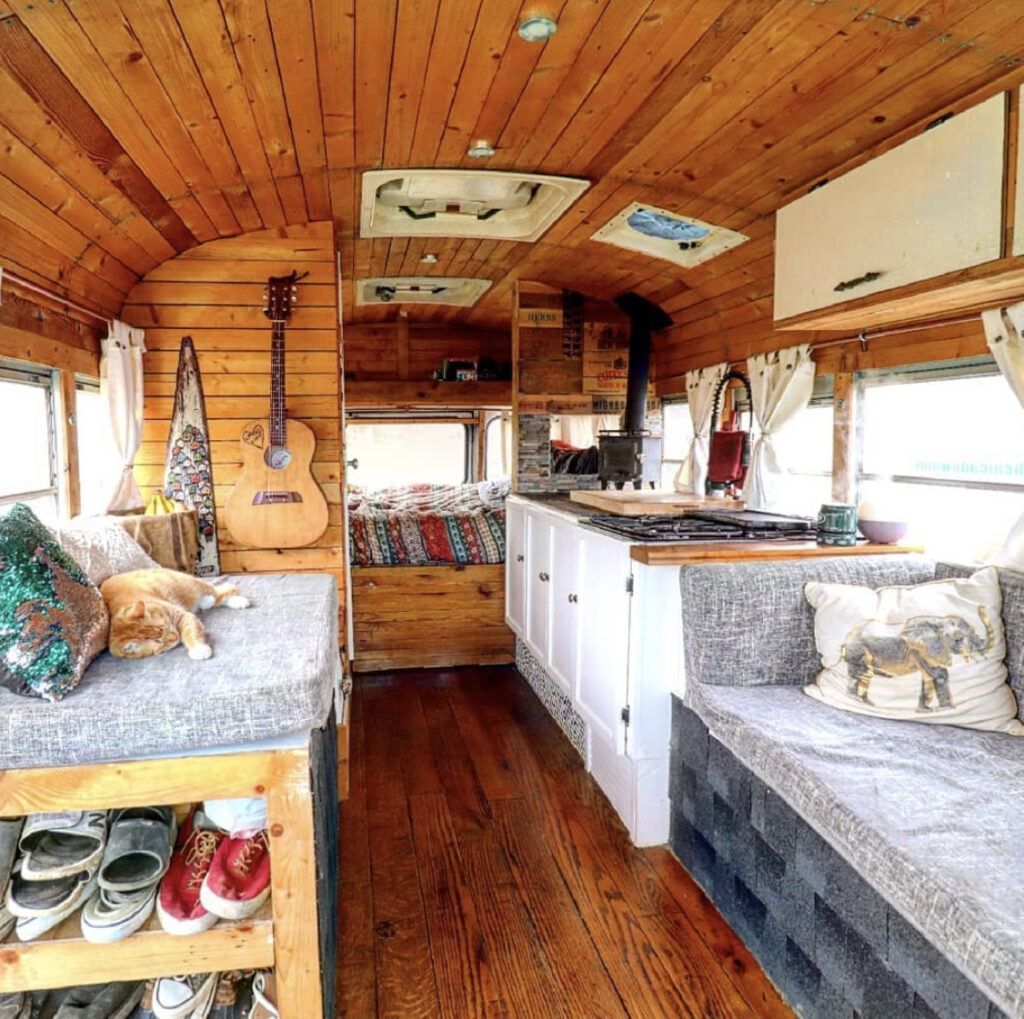 Bus interior with wooden walls, white kitchen and bes at back. Cat loungin on sofa