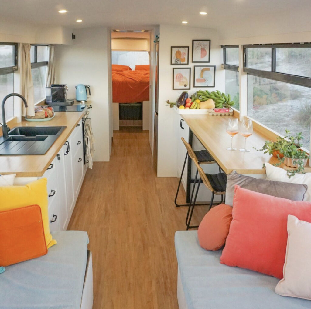 Modern and stylish bus, white walls and colourful cushion accents throughout