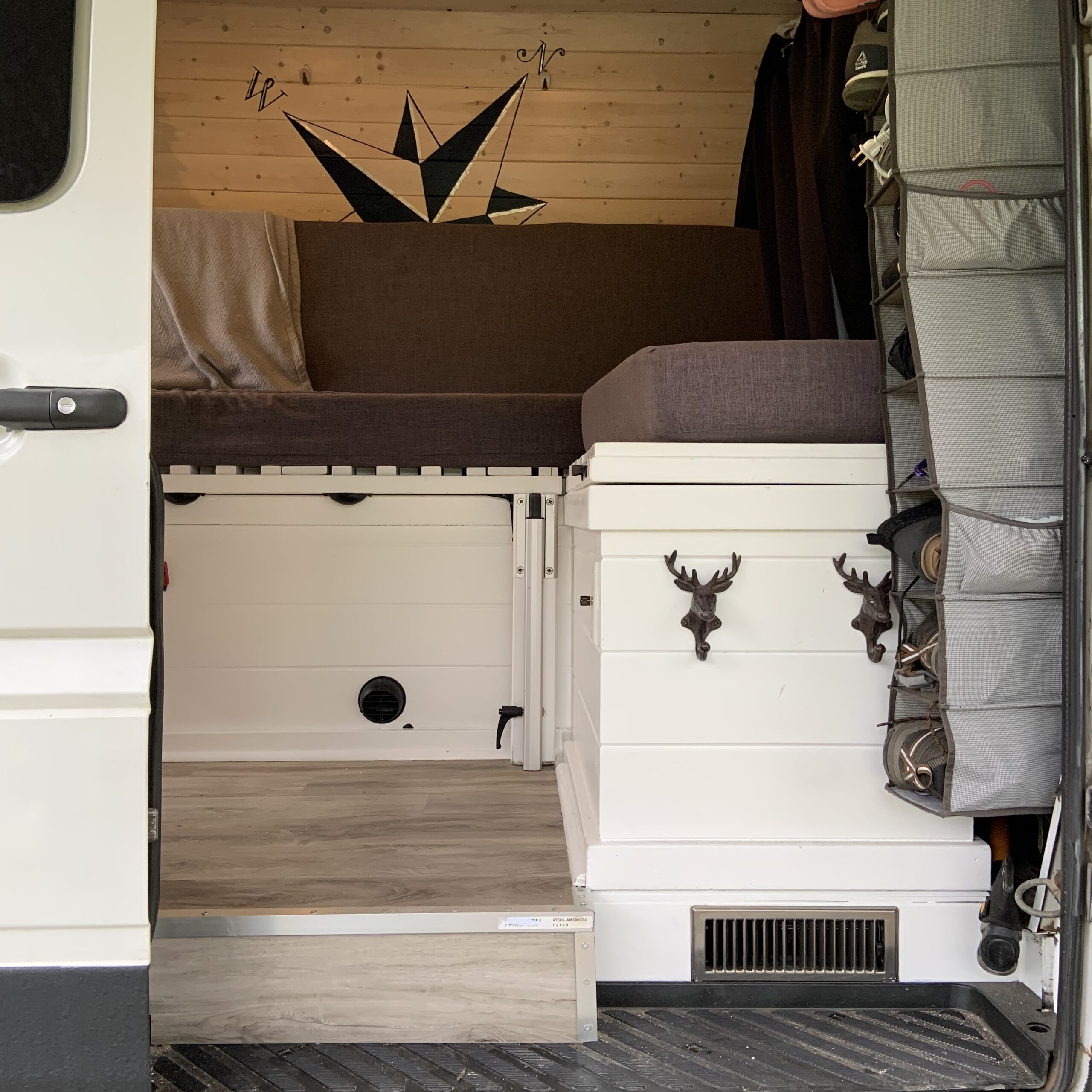 Looking into the van as the sliding door is open. The bench and bed set up is in clear view.