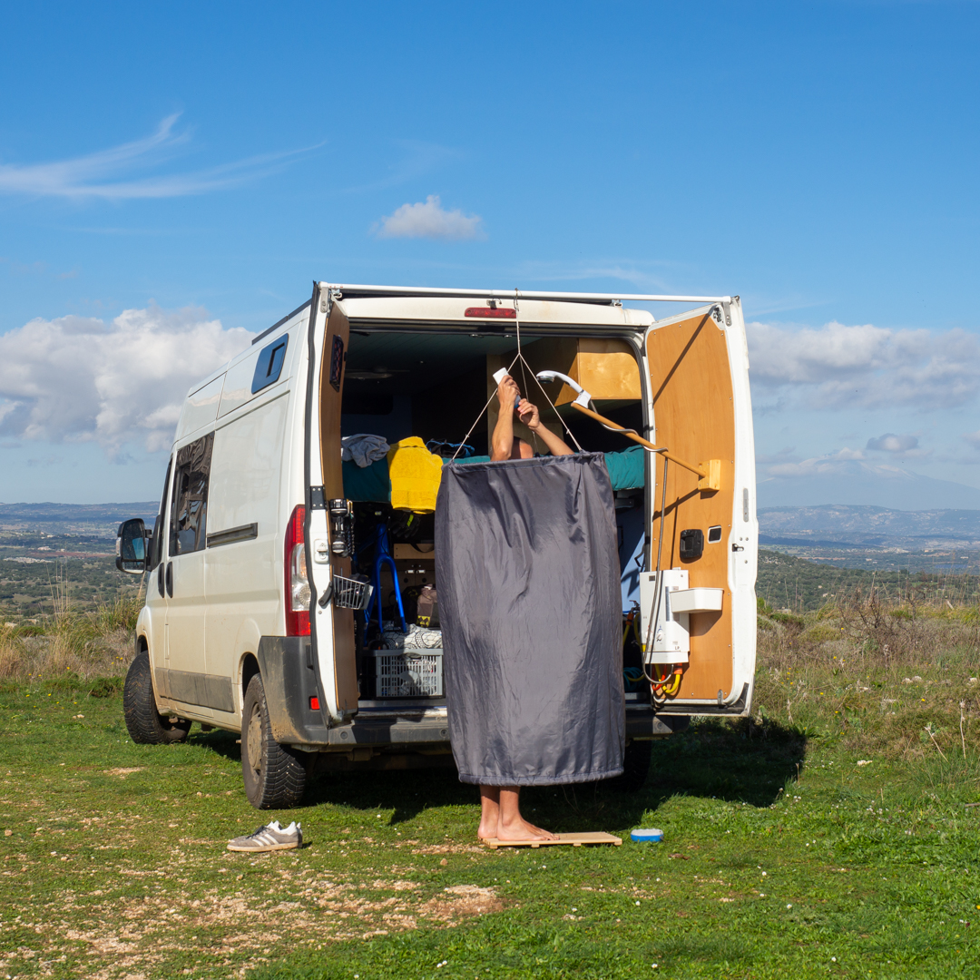 Outdoor shower with circular shower curtian at back of a van