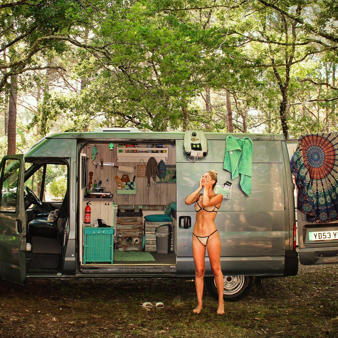 Solar shower in use on a van
